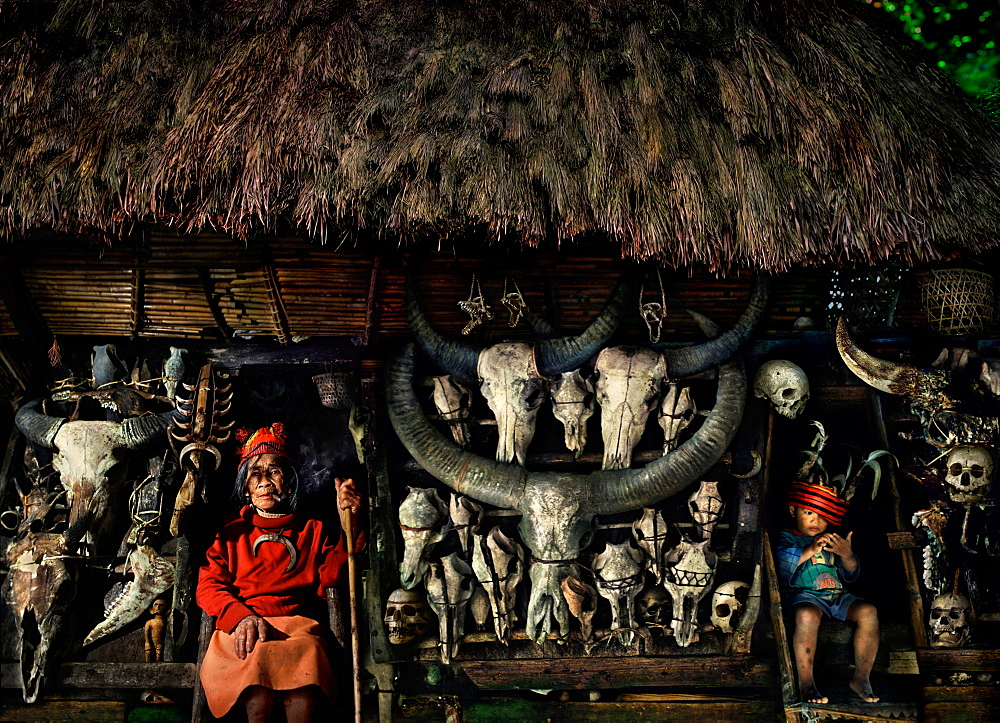 Senior woman and boy with human and water buffalo skulls, Banaue, Ifugao, Philippines