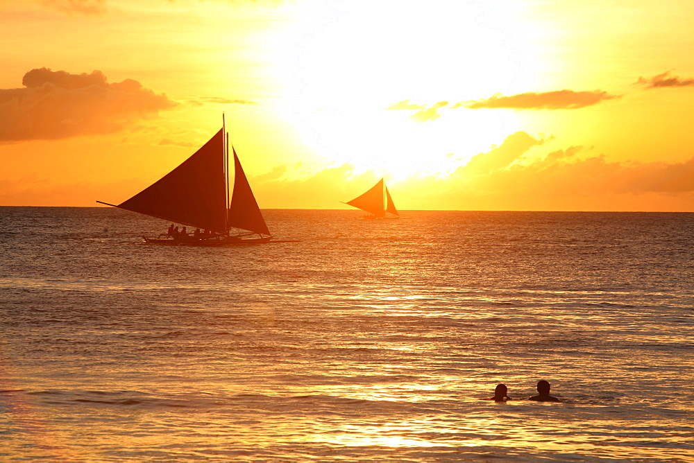 Tranquil scene with sailboats in sea at sunset, Boracay, Aklan, Philippines