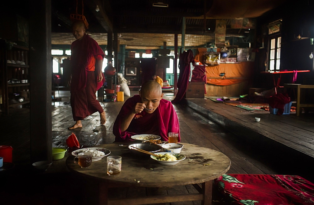 Young monk eating at table in rural monastery with another monk walking behind in background, Myanmar, Shan, Myanmar