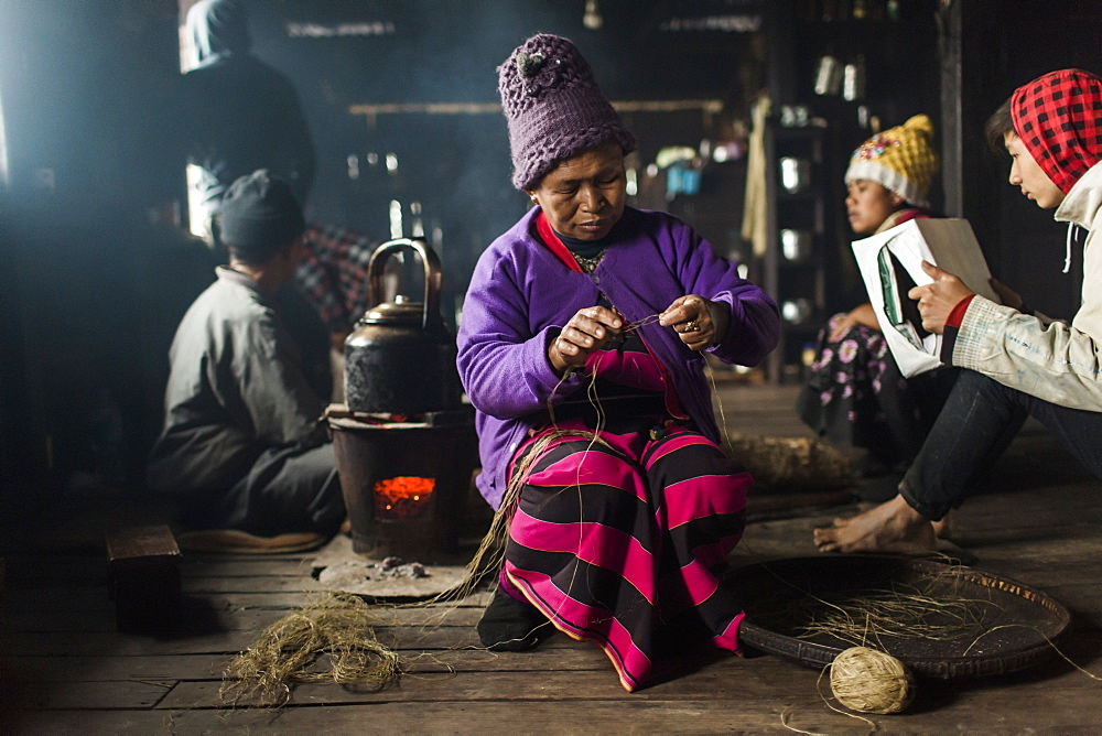 Elderly woman wearing knit hat knitting indoors in small rural house, Myanmar, Shan, Myanmar