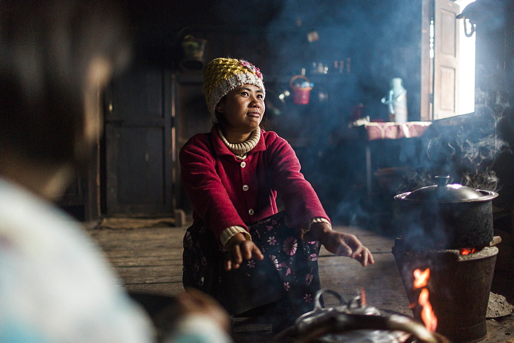 Young woman crouching in front of indoor campfire and warming hands, Myanmar, Shan, Myanmar
