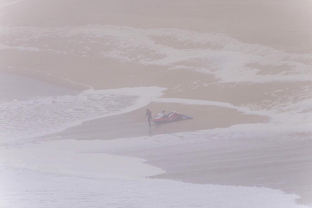 Man in fife jacket leading rescue jet ski in water at beach of Praia Norte, Nazare, Leiria, Portugal