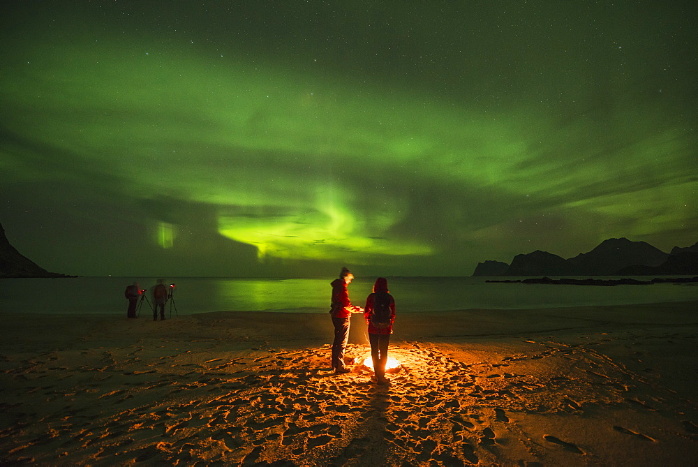 Tranquil scene with people around campfire on beach under aurora?borealis?at night, Flakstadoya, Lofoten Islands, Norway