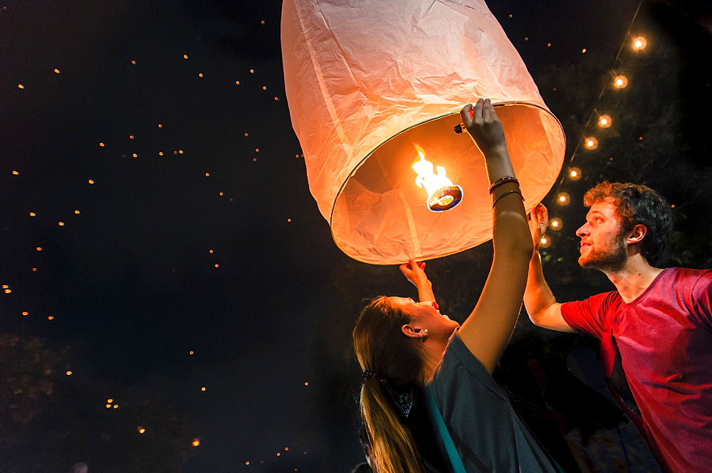 Man and woman holding paper lantern during Yi Peng festival, Chiang Mai, Thailand - 857-95996