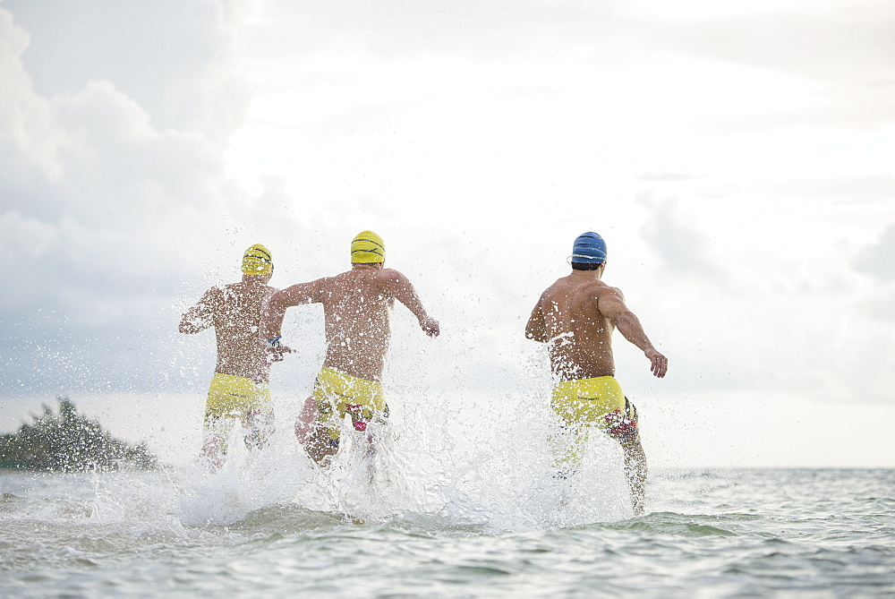 Rear view of three men in swimming caps and swimming trunks running into sea at Playa del Carmen, Quintana Roo, Mexico - 857-95998