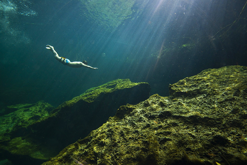 Distant view of single man?freediving?in?cenote?in Riviera Maya,?Quintana?Roo, Mexico - 857-95999
