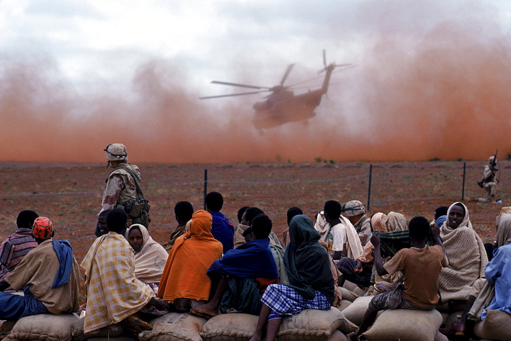 Food is airlifted by a helicopter to a food distribution site, Somalia.