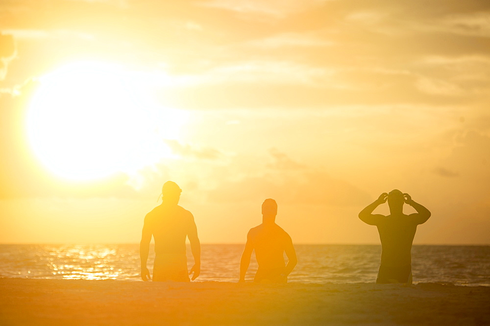 View of silhouettes of three men in swimming caps on beach at sunrise,?Playa?del?Carmen,?Quintana?Roo, Mexico