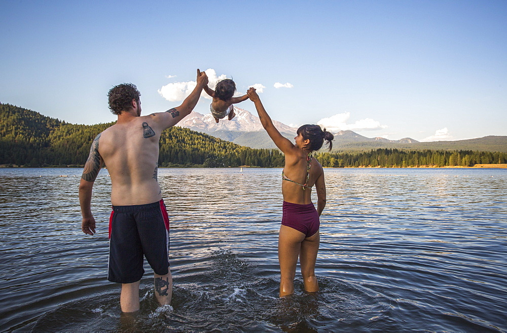 Rear view of couple in swimsuits playing with baby daughter in Lake Siskiyou, California, USA
