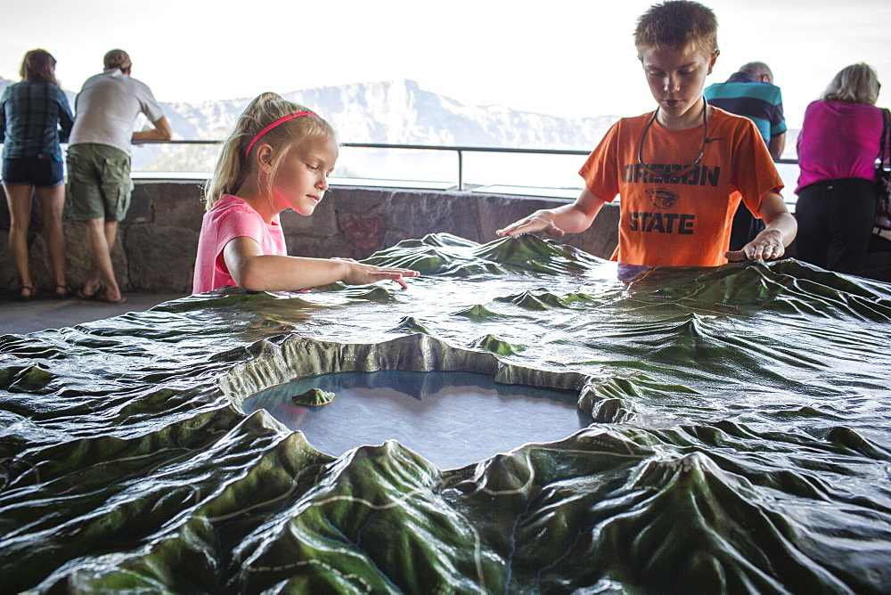 A young boy and a young girl stand at model map of Crater Lake with the real Crater Lake in the background, Oregon, USA