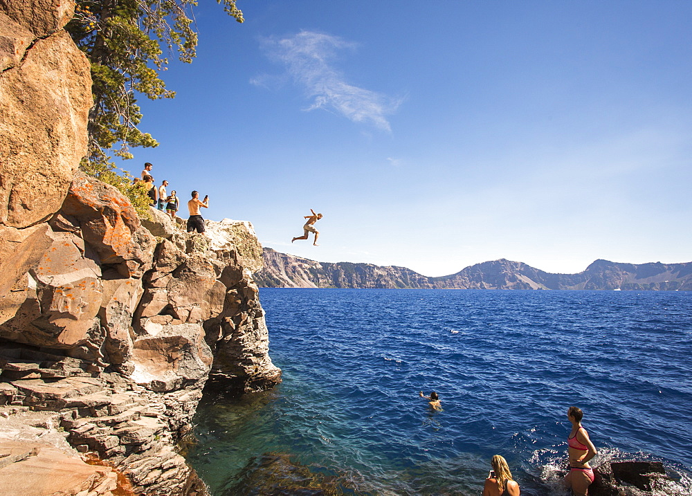 Young people wait on a rock outcrop and swim or jump into the deep blue waters of a mountain lake, Crater Lake, Oregon, USA - 857-96011