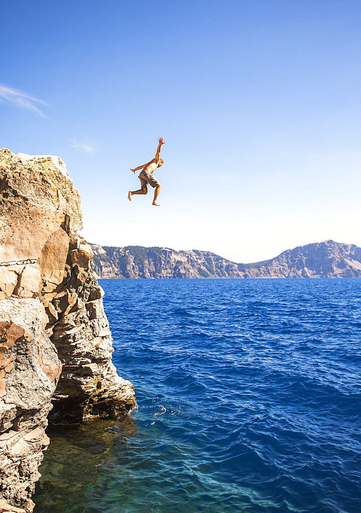 View of man in mid-air while cliff jumping into Crater Lake, Oregon, USA - 857-96012