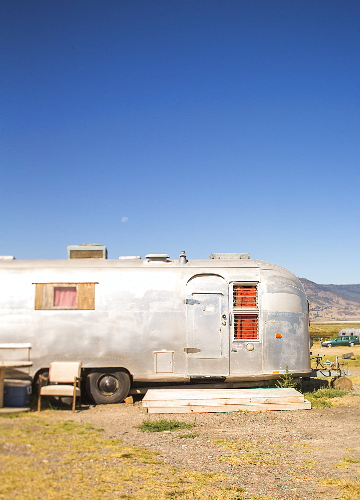 Side view of single camper trailer in desert under clear sky, Summer Lake, Oregon, USA