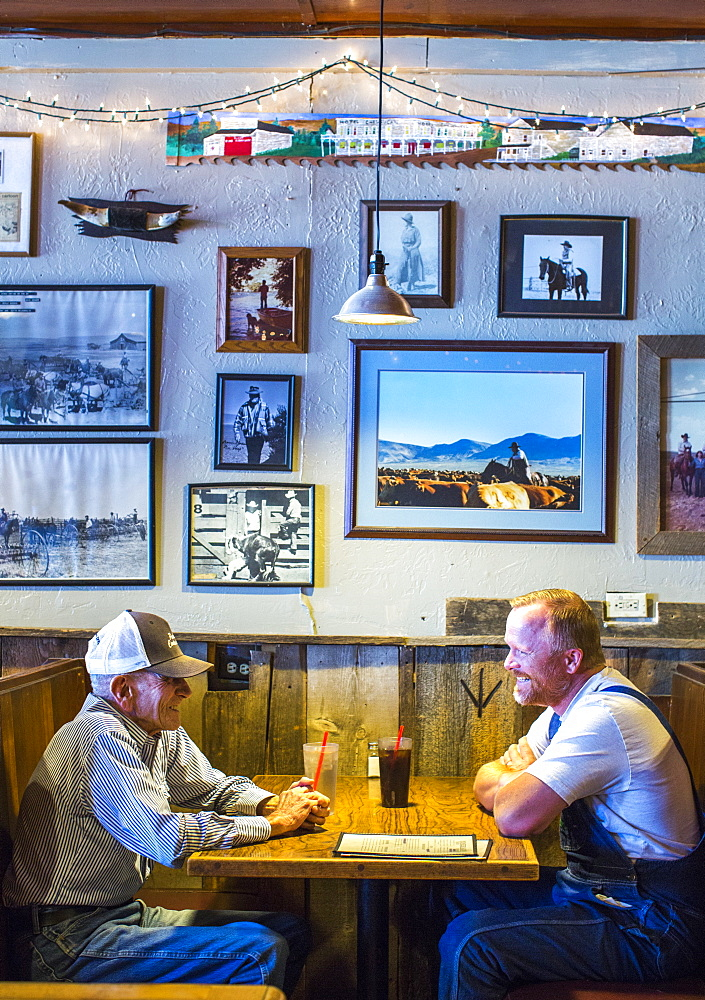 Side view of two mature men sitting at table in restaurant, Paisley, Oregon, USA