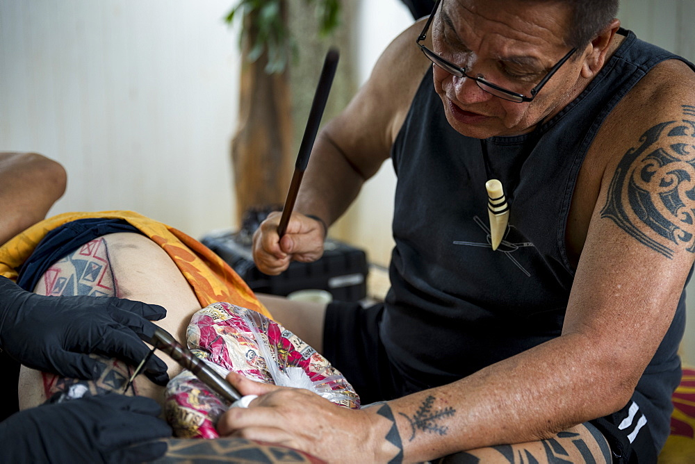 Side view of Hawaiian tattoo artist making tattoo, Oahu, Hawaii Islands, USA - 857-96028