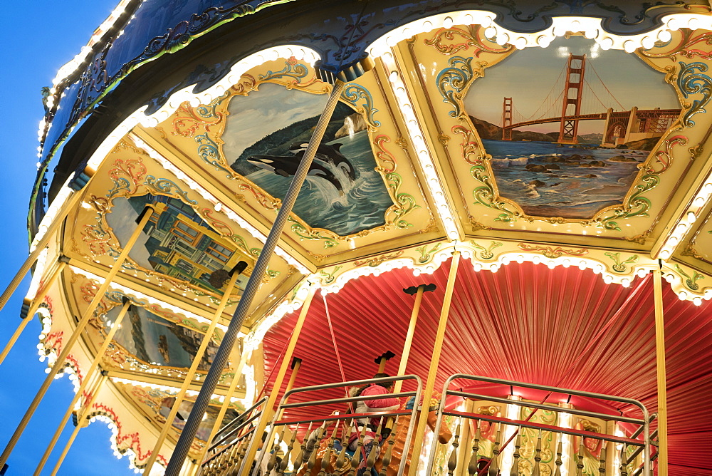 An old carousel, painted with life scenes of San Francisco in an end-of-day light, Pier 39, San Francisco, California, USA