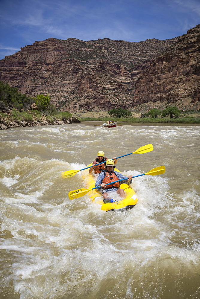 A man and woman paddling an inflatable kayak through rapids on a Green river rafting trip, Desolation/Gray Canyon section, Utah, USA