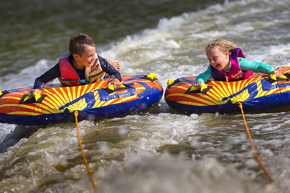 Front view of two children having fun tubing on river