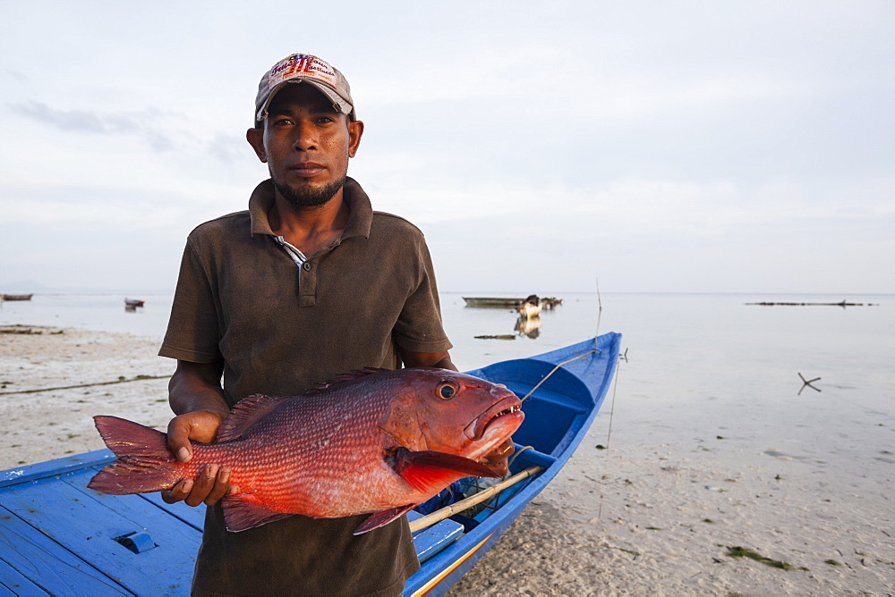 Fisherman showing a fish - Grogos Island Maluku Indonesia