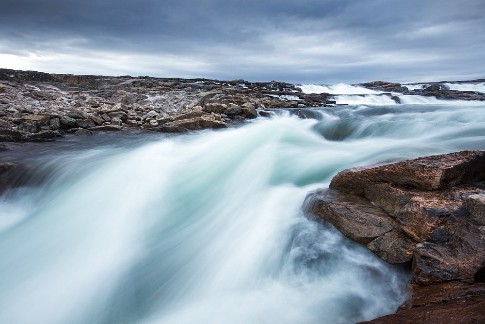 Blurred image of rushing waterfall near Bury Cove along west coast of Hudson Bay (Barren Coastline) 100 miles south of the Arctic Circle, Nunavut Territory, Canada