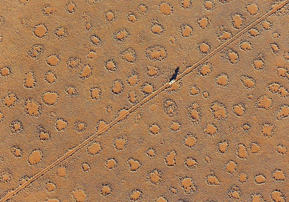 A vehicle of the balloon ground crew tries to follow the flight direction of the hot-air balloon, crossing a sandy plain at the edge of the Namib Desert. The so-called 'Fairy Circles' are circular patches without any vegetation which according to recent s