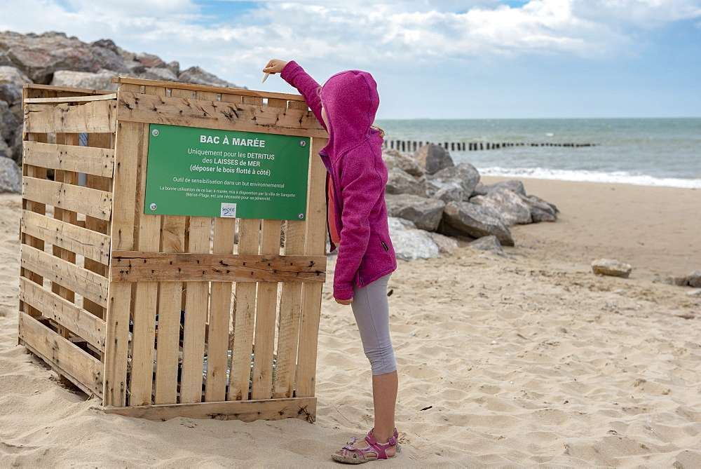 Girl throwing a plastic waste in a tidal bin on a beach on the Opal Coast, summer, Pas de Calais, France