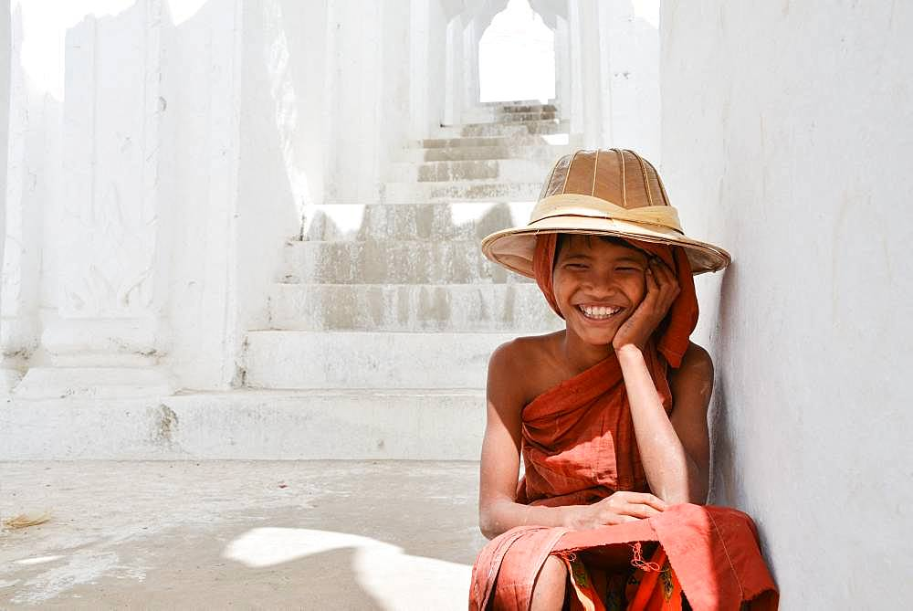 Teenager disguised as a monk playing on the steps of a pagoda in Burma in the city of Mandalay