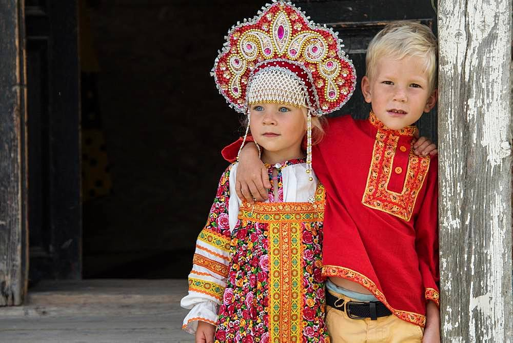 Little Russian girl and her brother in the town of Uglish in traditional dress at a village party