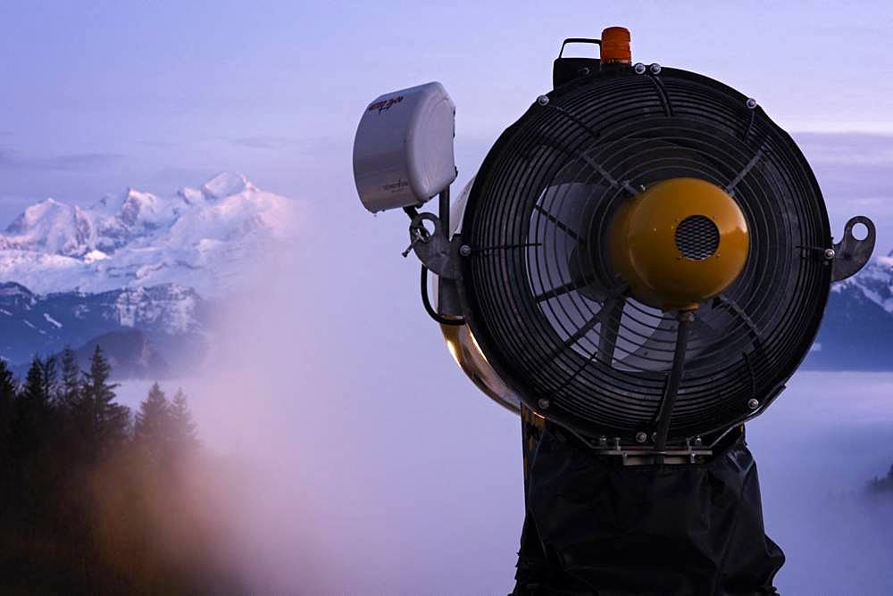 Snow cannon in action and Mont Blanc Massif, at sunset, seen from the station of Brasses, Haute-Savoie, Alps, France