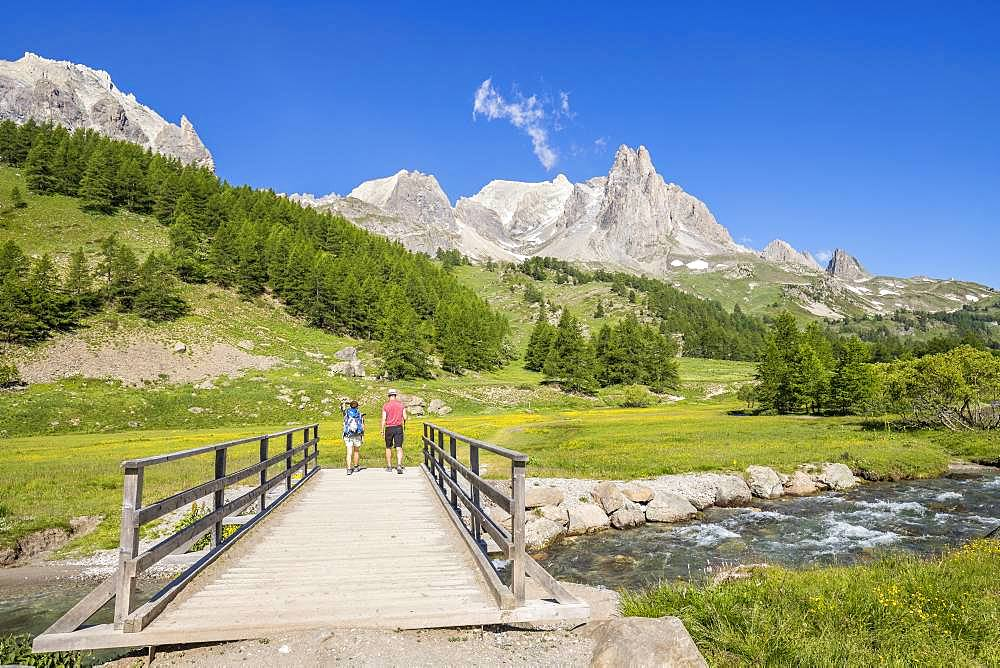 Vallee de La Claree, hikers on the Pont du Moutet, in the background the massif of Cerces (3093m) and the peaks of the Main of Crepin (2942m), Nevache, Hautes-Alpes, France