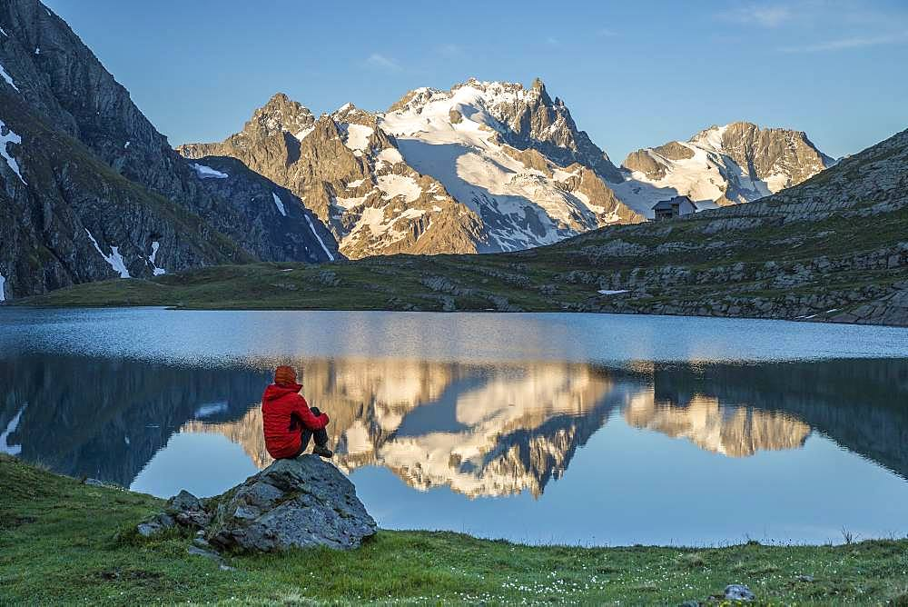 A hiker sitting on a rock contemplates the landscape at the edge of Lake Goleon (2438m) in the massif of Oisans with in the background the Meije (3983m) and the Rake (3809m), Ecrins National Park, Hautes-Alpes, France