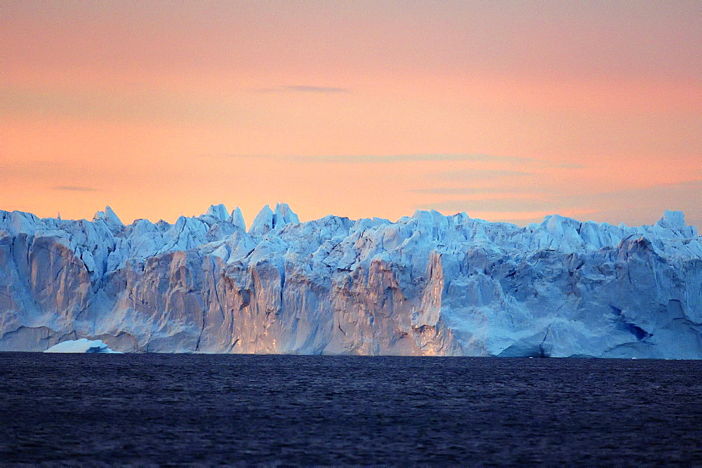 Serac at sunset, a huge serac of a hundred meters long and 30 meters high has just detached from a glacier front at the bottom of Scoresby Sund, It will break into several large icebergs, Greenland