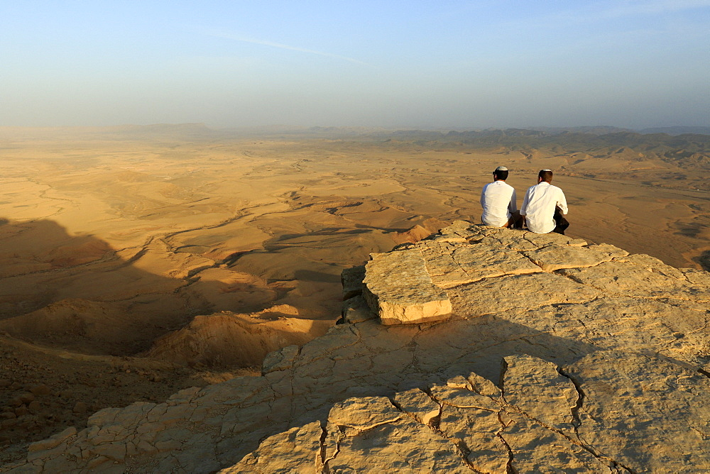 Tourists on the edge of Makhtesh ramon, karstic erosion circus in the Negev desert, Mitzpe ramon, Israel.