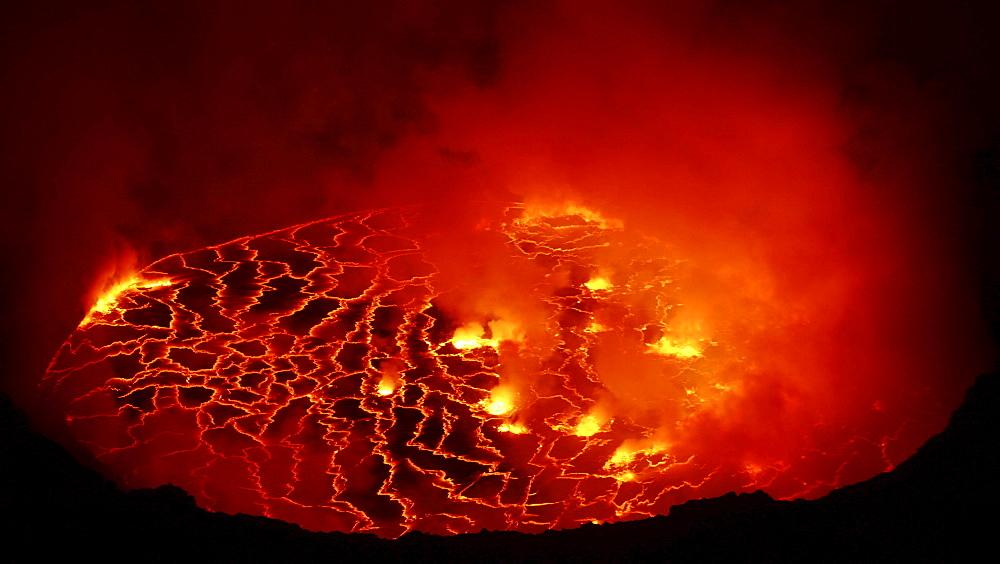 volcano Nyiragongo crater with lava fountains in the lava lake rising smoke nature natural phenomenon night view Kongo Afrika