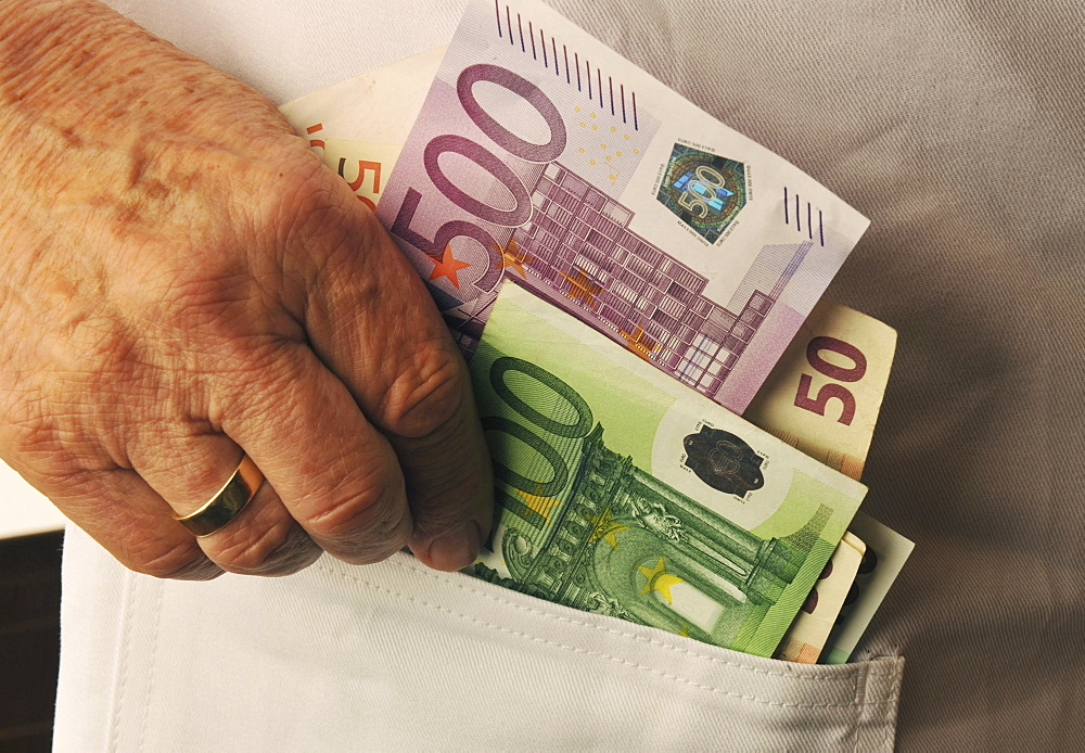 doctor putting Euro bank notes in pocket portrait symbol