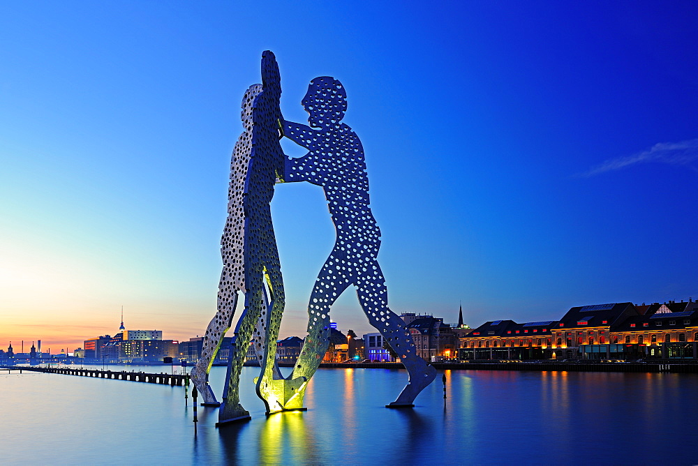sculpture Molecule men 30 meter tall work made of aluminium by artist sculptor Jonathan Borofsky illuminated standing in river Spree at sunset mood Berlin Germany - 869-5580