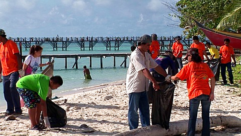 School children cleaning rubbish on the beach. Sipadan Water Village, Mabul, Borneo, Malaysia