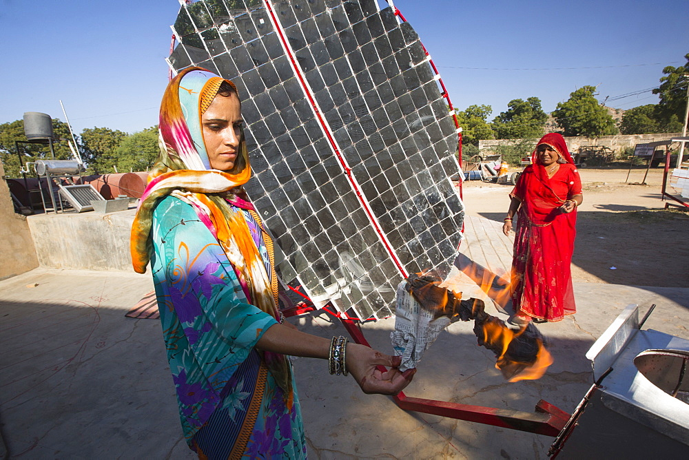 Women constructing solar cookers at the Barefoot College in Tilonia, Rajasthan, India, demonstrate how hot the device is, by holding a sheet of newspaper which instantly sets on fire in the 300 degree Celcius heat. The Barefoot College is a worldwide charity, founded by Bunker Roy, its aims are, education, drinking water, electrification through solar power, skill development, health, women empowerment and the upliftment of rural people. The use of the cookers, vastly reduces the amount of fire wood women have to go out and collect from the forest. - 911-10044