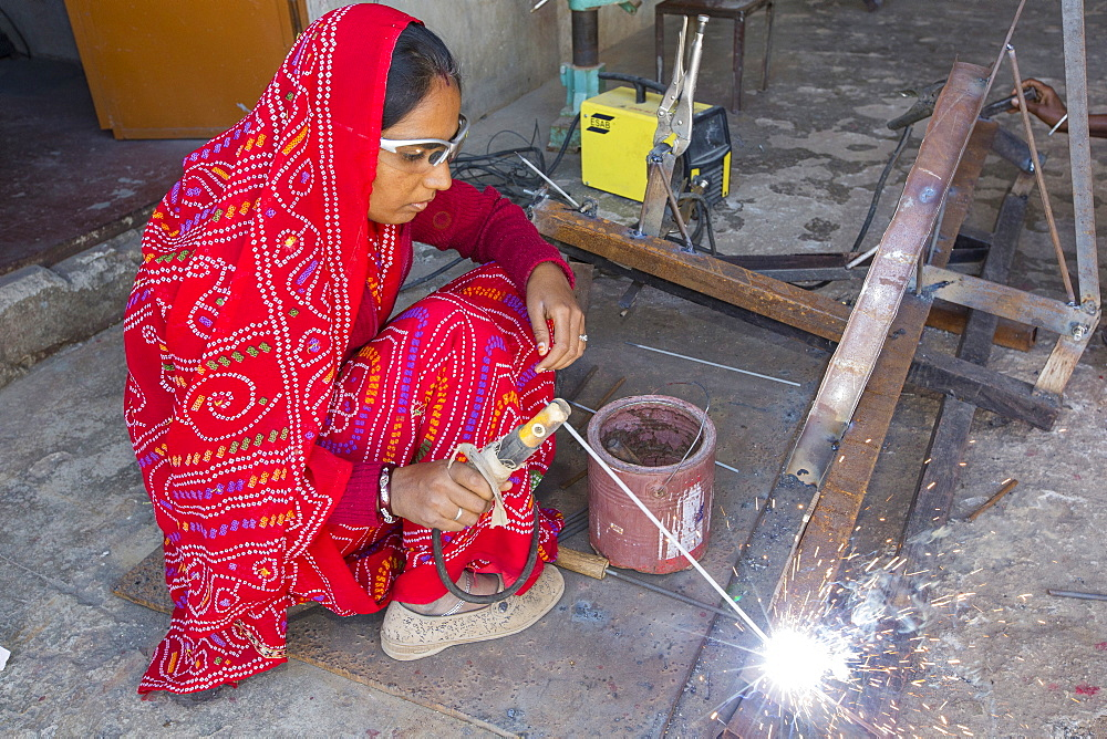 Women welding joints during the construction of solar cookers at the Barefoot College in Tilonia, Rajasthan, India. The Barefoot College is a worldwide charity, founded by Bunker Roy, its aims are, education, drinking water, electrification through solar power, skill development, health, women empowerment and the upliftment of rural people. Solar cookers save women having to walk to the froest to cut down wood for cooking, thus saving the forests, and a daily chore for woman.
