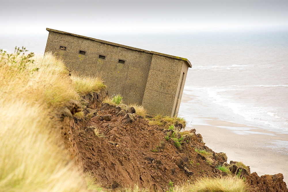 A Second world War lookout post leaning alarmingly and about to tumble over the edge of the cliff near Aldbrough on Yorkshires East Coast, UK. The coast is composed of soft boulder clays, very vulnerable to coastal erosion. This section of coast has been eroding since Roman times, with many villages having disappeared into the sea, and is the fastest eroding coast in Europe. Climate change is speeding up the erosion, with sea level rise, increased stormy weather and increased heavy rainfall events, all playing their part.