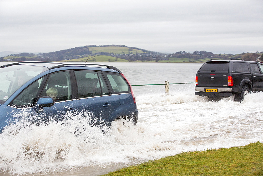 A motorist travels through flood waters on the road at Storth on the Kent Estuary in Cumbria, UK, during the January 2014 storm surge and high tides.