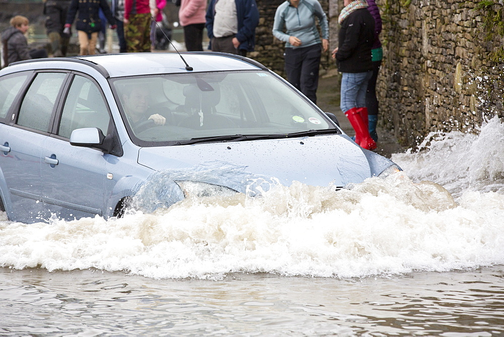 A motorist travels far too fast through flood waters on the road at Storth on the Kent Estuary in Cumbria, UK, during the January 2014 storm surge and high tides.