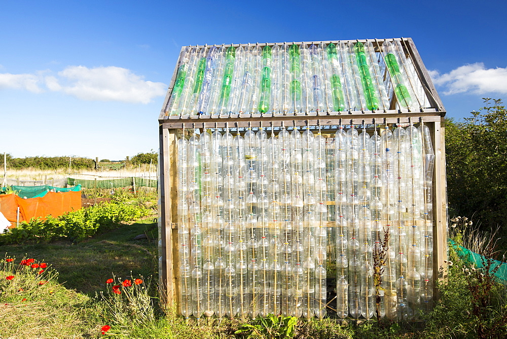 A greenhouse made from waste plastic drinks bottles in the community garden at Mount Pleasant Ecological Park, Porthtowan, Cornwall, UK.