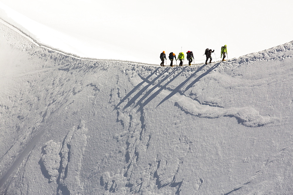 Climbers on the arete leading up from the Vallee Blanche to the Aiguille Du Midi above Chamonix, France.