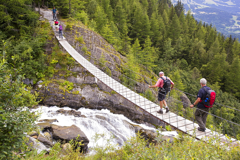 Walkers on the Tour Du Mont Blanc cross a suspension bridge across the meltwater river from the Bionnassay glacier;