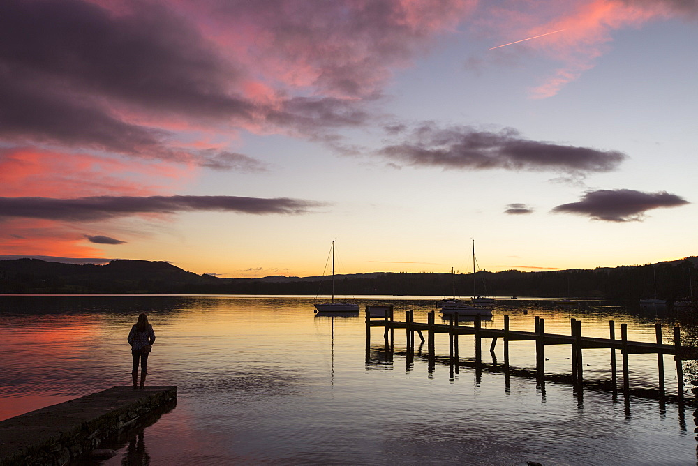 A woman by Lake Windermere at sunset, Ambleside, Lake District, UK.