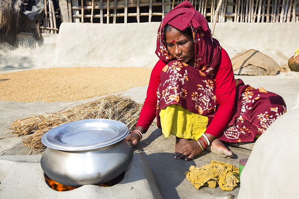 A woman subsistence farmer cooking on a traditional clay oven, using rice stalks as biofuel in the Sunderbans, Ganges, Delta, India. the area is very low lying and vulnerable to sea level rise. All parts of the rice crop are used, and the villagers life is very self sufficient, with a tiny carbon footprint.
