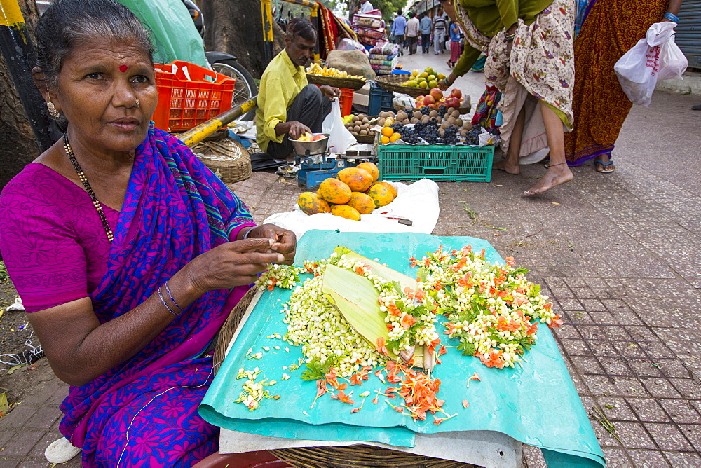 A woman making floral hair decorations at a street market in Mysore, India.