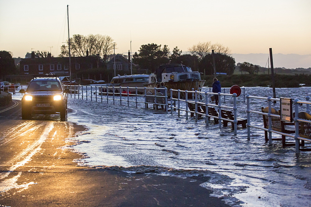 A high tide pushed by gale force winds flooding the sea front in Blakeney, Norfolk, UK.