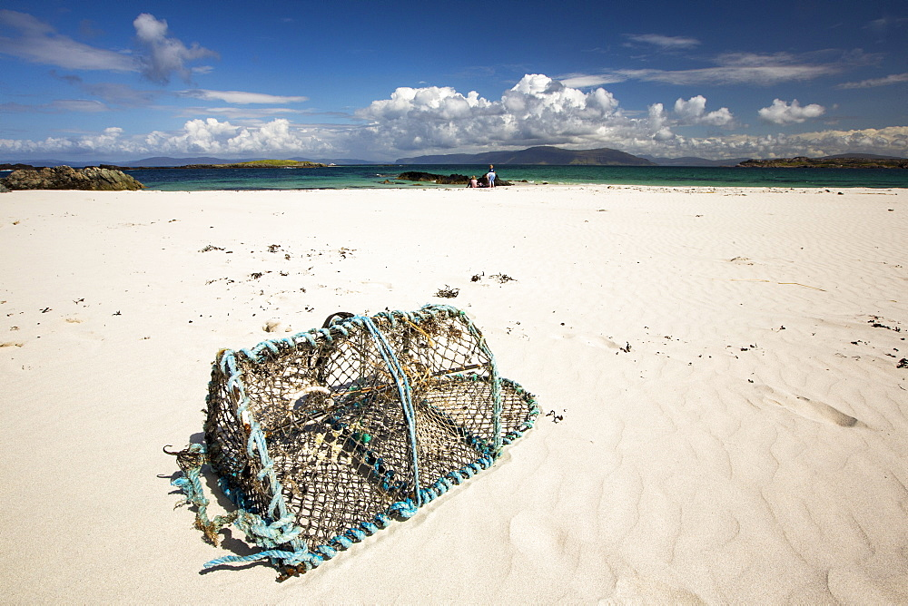 White sand beaches and clean seas on the north coast of Iona, off Mull, Scotland, UK, with a lobster pot washed ashore.